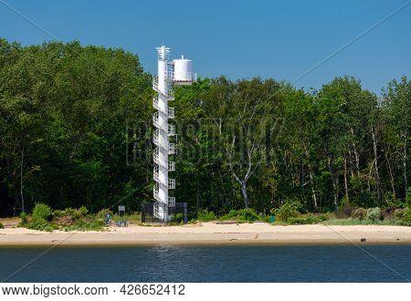 Swinoujscie. Lighthouse On A Sunny Day Against The Blue Sky.