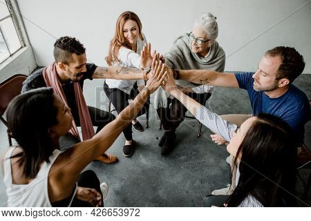Group of diverse team joining hand in the middle