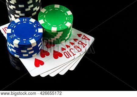 Poker Game With Royal Flush Combination. Chips And Cards On The Black Table. Successful And Maximum