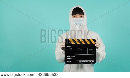 Black And Yellow Clapperboard Or Movie Slate.asian Woman Wear Face Mask And Ppe Suit On Mint Green O