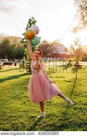 Portrait Of Slender Ballerina In A Pink Silk Dress And White Pointe Shoes, Standing And Balancing On