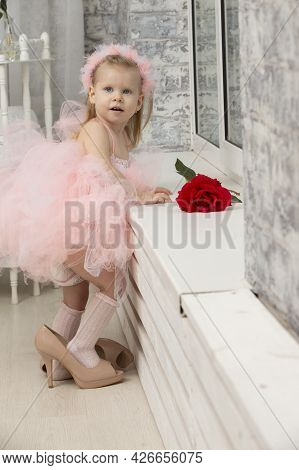 Little Funny Girl In A Smart Pink Dress And High Heel Shoes.