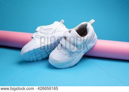 Two White Teen Sneakers With Velcro Fasteners For Comfortable Footwear On A Pink Long Paper Roll On