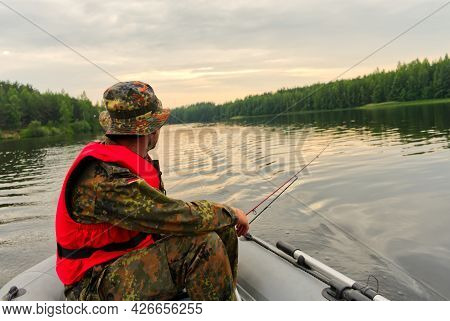 A Fisherman On An Inflatable Boat Catches Fish On Spinning. The Process Of Trolling On The Lake. Clo