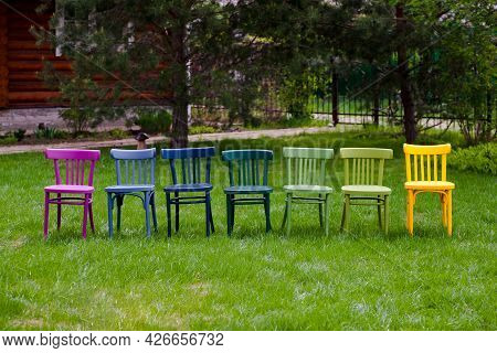 A Row Of Colorful Rainbow Wooden Chairs On A Green Lawn, An Lgbt Community Party In The Park In The