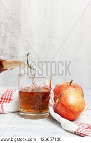 Squeezed Apple Juice Is Pouring In The Glass With Towel And Fresh Apples On Concrete White Backgroun