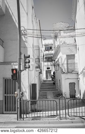 Street Scene With Steps Up Between Buildings With Power Lines Strung Across And Red Crossing Warning