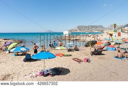 Altea Spain - August 24 2016; Summer Sunbathing Tourists On Mediterranean Beach And Under Umbreallas