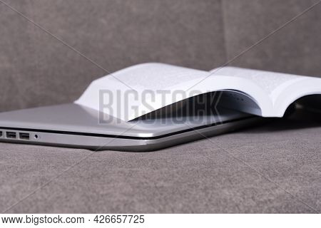 Laptop With Open Book To Read On Gray Sofa.