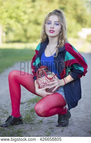 A Beautiful 90s Country Girl In Bright Clothes Holds A String Bag With A Can Of Birch Sap. Russian W