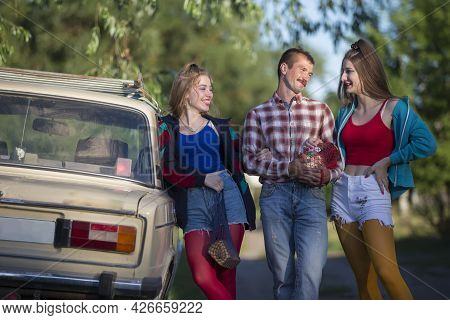 Handsome Girls And A Country Man Dressed In 90s Style Stand Near An Old Car.