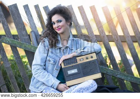 A Beautiful Country Girl In Bright Clothes Sits On A Wooden Bench With A Cassette Recorder. Woman In