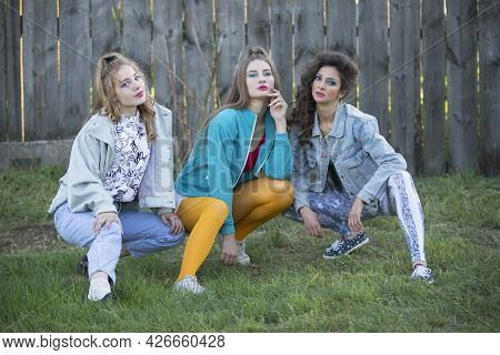 Funny Girls In The Style Of The 90s In Bright Clothes Are Sitting Near A Wooden Fence.
