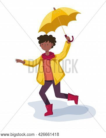Happy Cute African American Boy With Umbrella In Yellow Raincoat And Rubber Boots Walks Through The