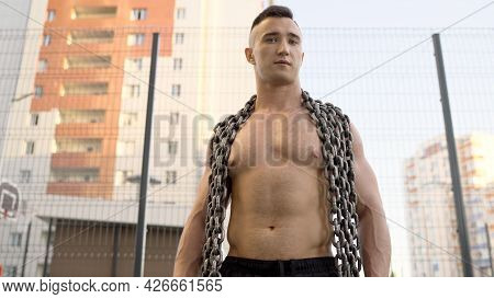 Athlete Stands With A Large Chain Around His Neck. An Athlete With A Chain On His Neck Stands On The