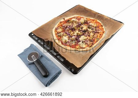 High Angle Studio Shot Of Homemade Pizza Al Tonno On Black Baking Tray And Baking Paper, Isolated On