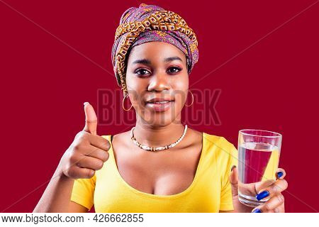 African Woman With Turban On Head And Yellow T-shirt Holding Glass With Pure Clean Water In Studio R