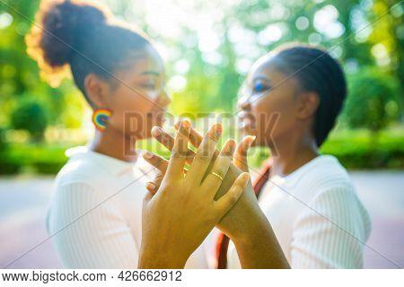 Brazilian Lesbian Couple In White Dress Spending Time Together Celebrating Engagement In Summer Park