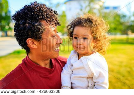 Young Pretty Dad And His Little Curly Daughter Hugging Outdoors At Sunset Light