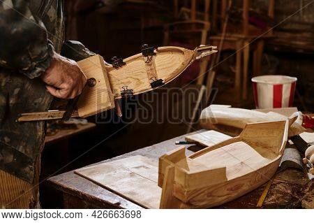 Wooden Models Of Ships On The Carpenter's Desk Against The Background Of A Working Craftsman. The Ma