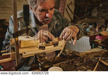 Carpenter Sticks A Wooden Part On A Wooden Ship. Craftsman In Workshop Making Wooden Toy, A Wooden M