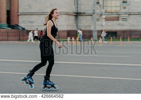Athletic Woman On Roller Skates Moves Actively Poses On Asphalt At Street Dressed In Active Wear Has