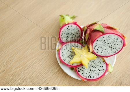 Slices Of Dragon Fruit Or Pitaya With White Pulp And Black Seeds On White Plate With One Slice Of St