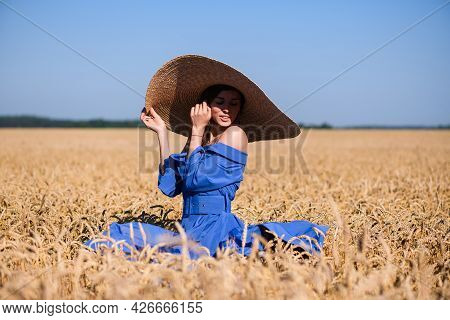 Romantic Young Girl Hide Face Under Wide Brim Hat, Wearing Blue Dress, Stay In Wheat Field, Natural