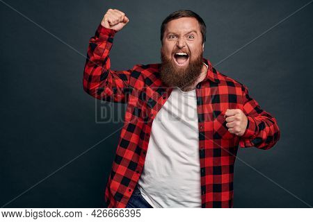 Triumphing Young Bearded Guy Feeling Like Champion Of World, Celebrating Success Or Win, Yelling Yes