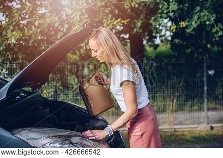 The Blonde Woman Refills The Oil In Her Car.