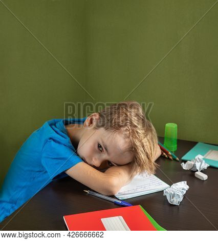 Sad And Tired Caucasian Boy Schoolboy Does Lessons At The Table. Crumpled Scribbled Sheets From The