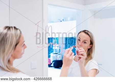 Inscription Im Sorry By Lipstick On Mirror And Reflection Of A Woman