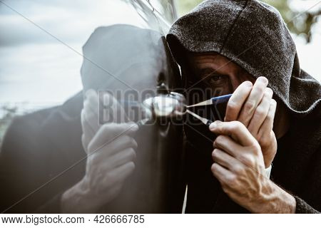 A Car Thief Opening A Car Door With A Lockpicer.