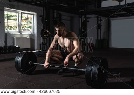 Young Active Strong Fit Sweaty Muscular Man Wit Big Muscles Sitting On The Floor Of The Gym After Ba