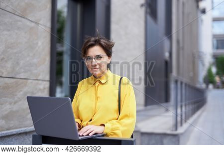 Portrait Of Young Charming Businesswoman In Eyeglasses And Yellow Blouse Standing At The Street In D
