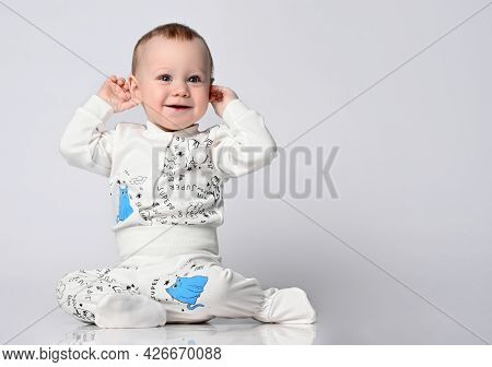 Cute Blue-eyed Baby In A White Sandpit Bodysuit With A Kitten Print, Sits On The Floor And Touches A