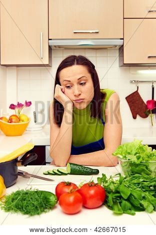 weary housewife standing in kitchen