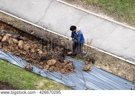 Migrant Labor. A Worker Digging A Ditch Along A Pavement In Summer.