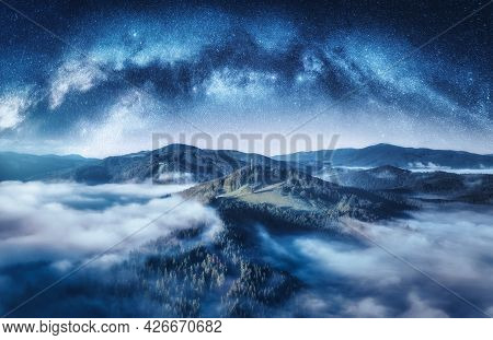 Milky Way Arch And Mountains In Low Clouds At Starry Night
