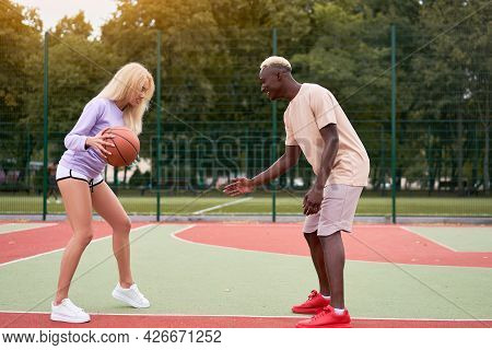 Active Multiethnic Couple Playing Basketball On Outdoor Sport Court, Black Guy Teaching His Cute Blo