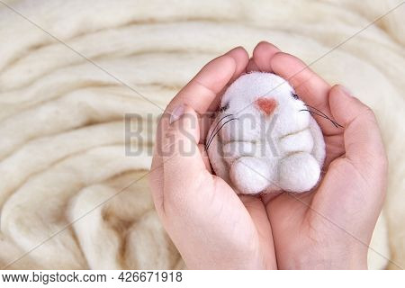 Cute Felted Bunny In The Hands Of A Woman On A Background Of Wool.