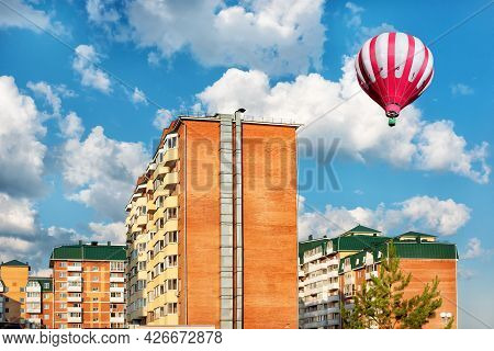 New High-rise Buildings With A Hot Air Balloon Under Blue Cloudy Sky. Urban View.