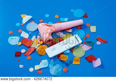 a covid-19 antigen diagnostic test device, a pink party horn and some multicolored confetti on a blue background, as a safe party set