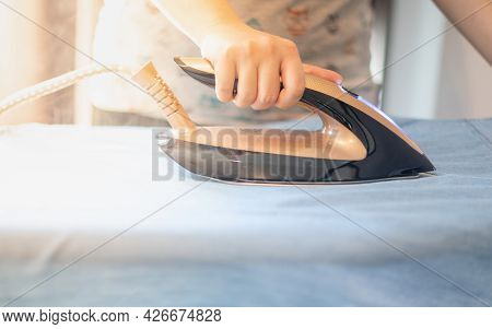 Female Hand Ironing Clothes On Iron Board At Home On The Laundry Day.
