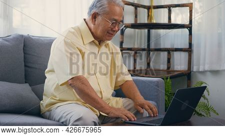 Senior Man Dressed Wear Eyeglasses Sitting On Sofa Working On Laptop In Living Room At Home, Happy O