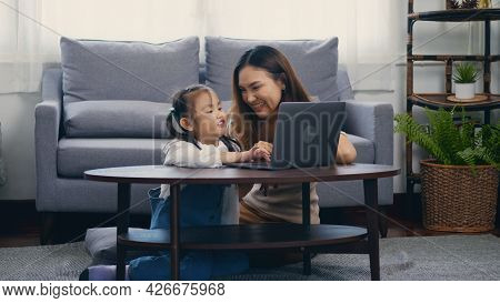 Asian Young Mother With Laptop Computer Teaching Her Kid To Learn Or Study Online In Living Room At