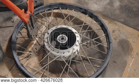 A Motorcycle Mechanic Man Using Iron Nippers. Cut The Spokes From The Wheels Alignment. For Weaving