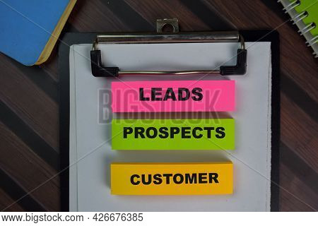 Leads Prospects Customer Write On Sticky Notes Isolated On Wooden Table.