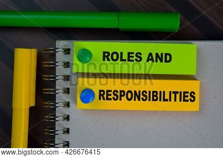 Roles And Responsibilities Write On Sticky Notes Isolated On Wooden Table.