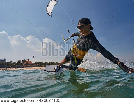Kite surfer riding a kiteboard on the sea with splash
